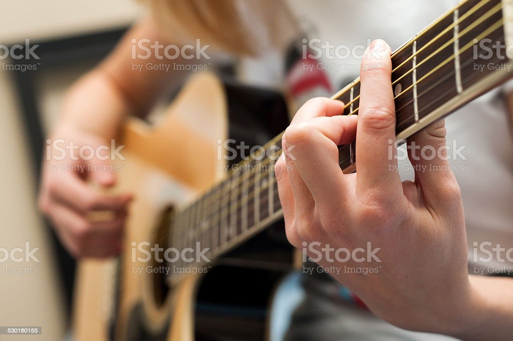 Student blonde girl playing yellow acoustic guitar close up....
