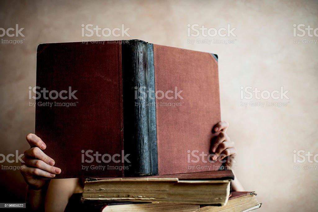 Unrecognizable person reading hardcover book. stock photo