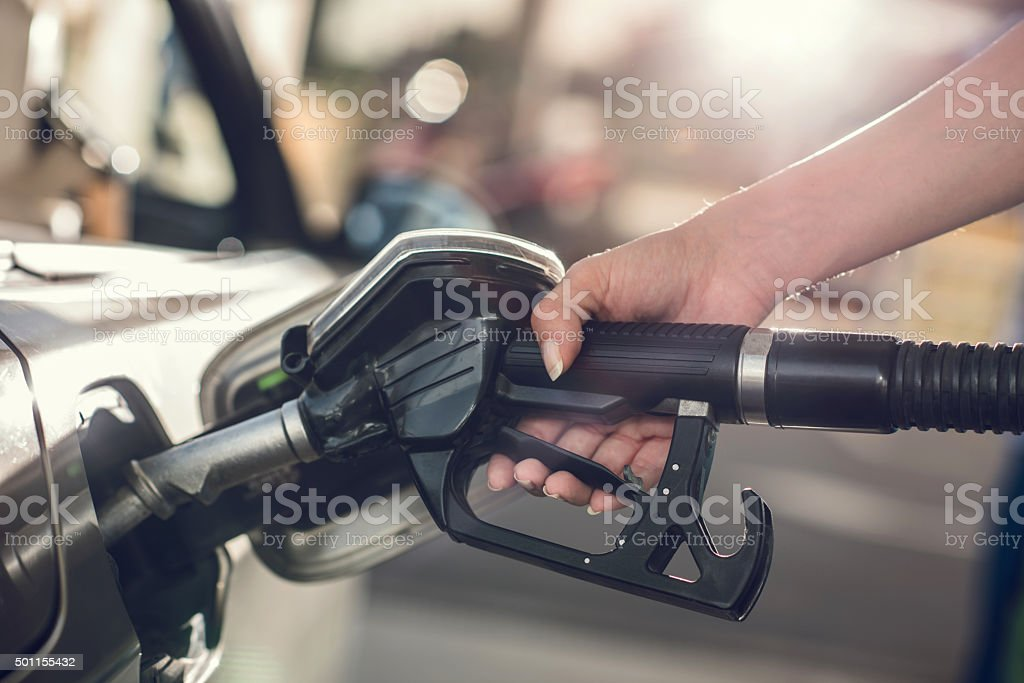 Unrecognizable person refueling gas into a gas tank. stock photo