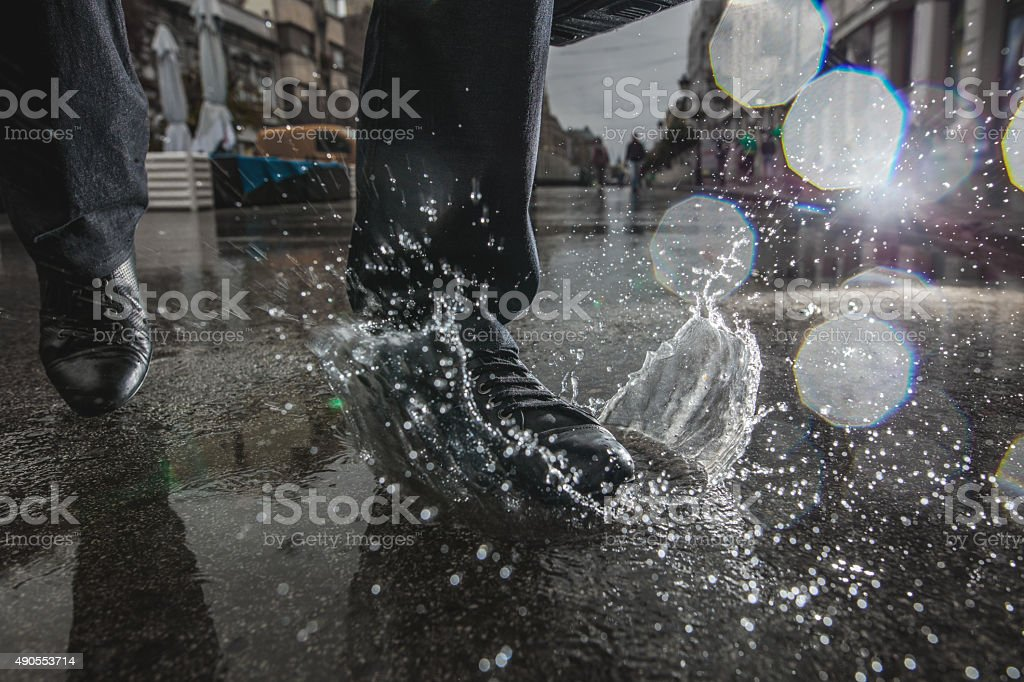 Unrecognizable person stepping into a puddle during rainy day. stock photo