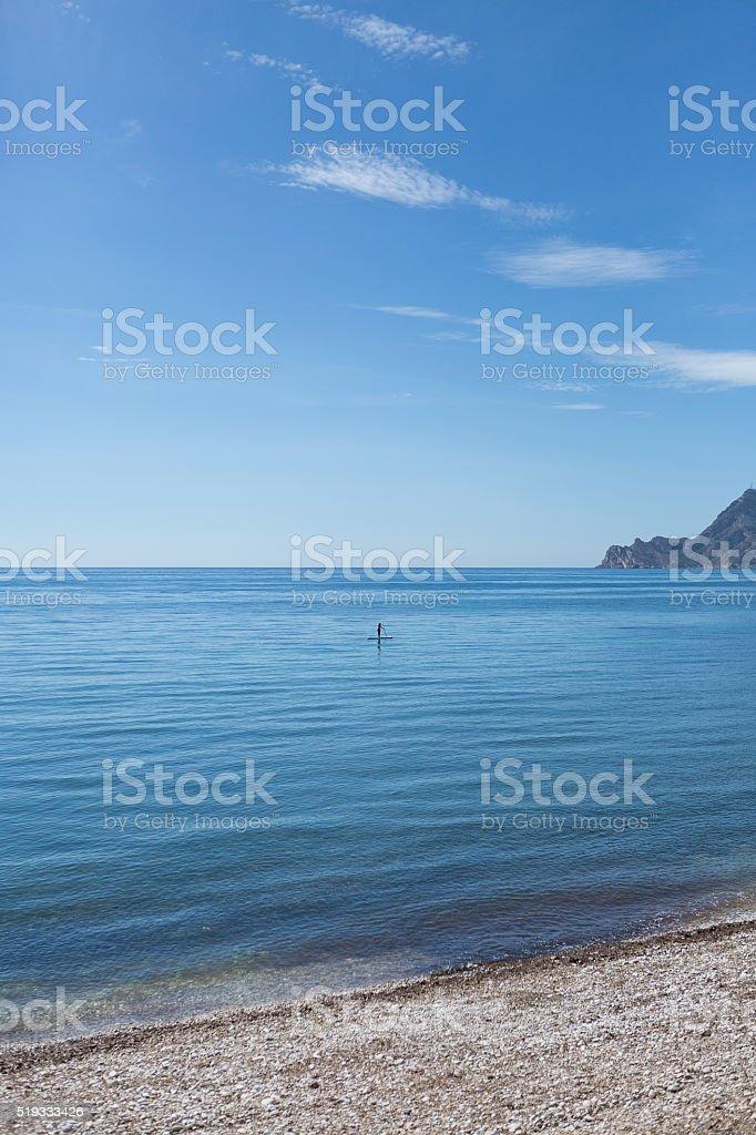 Unrecognizable person surfing alone in sea stock photo