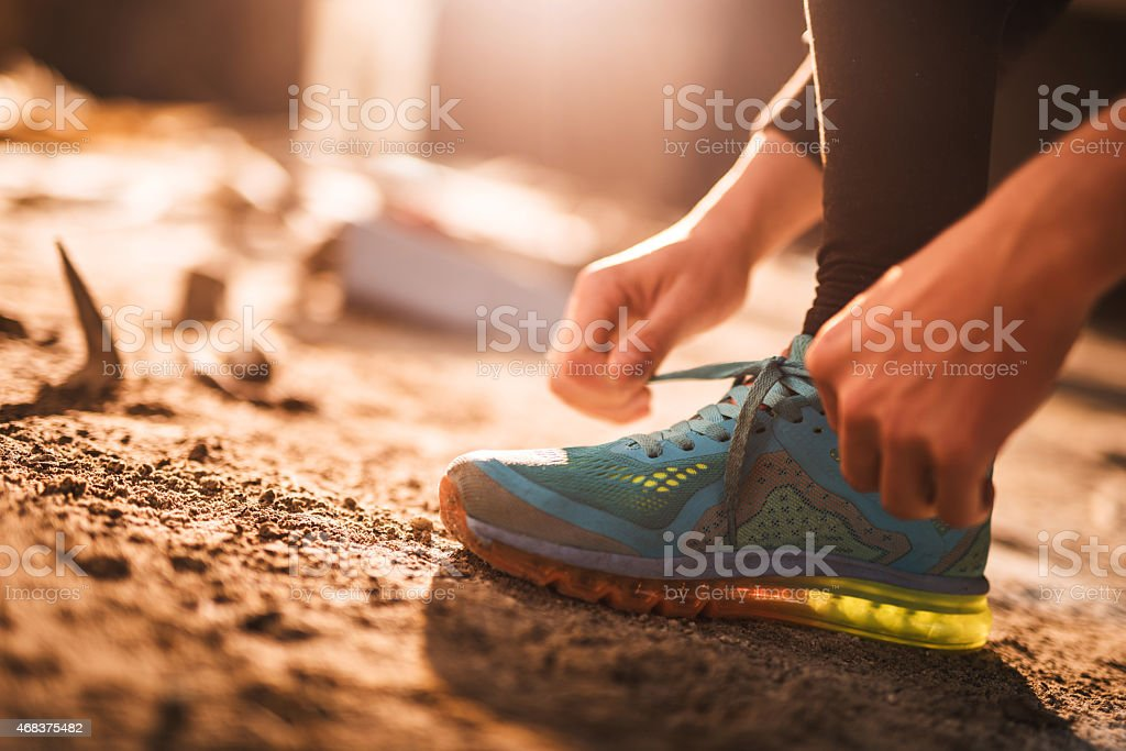 Unrecognizable athlete preparing for exercising and tying shoelaces.