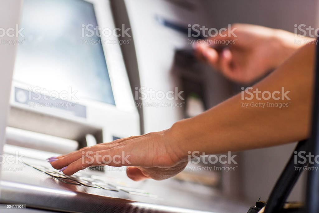 Unrecognizable person typing PIN on ATM. stock photo