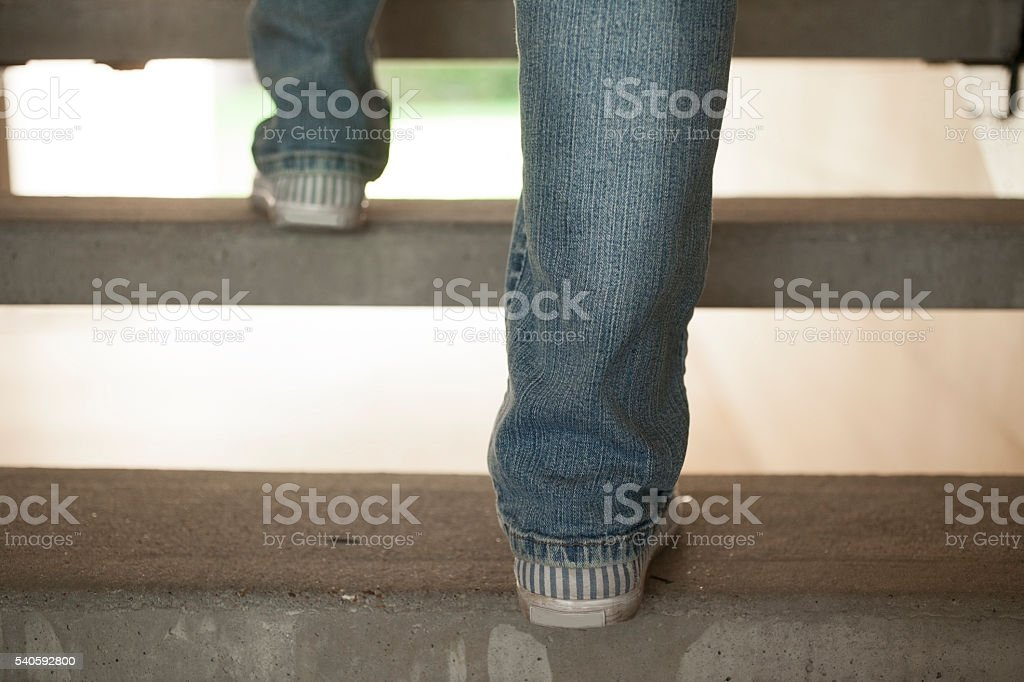 Unrecognizable person walking up stairs to apartment. stock photo