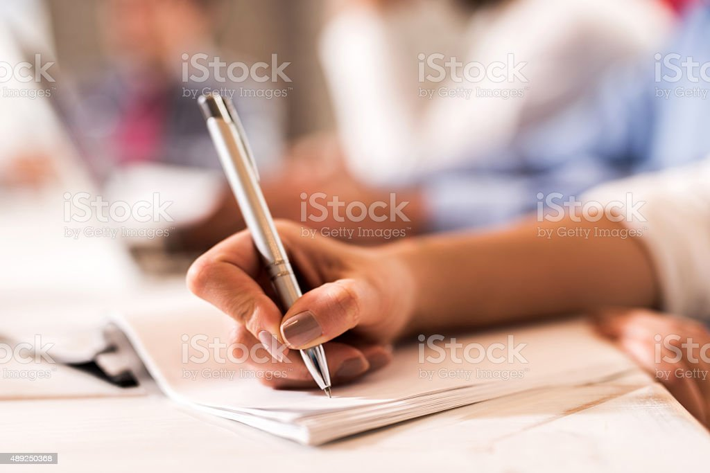 Close up of unrecognizable woman writing on a paper with a pen.