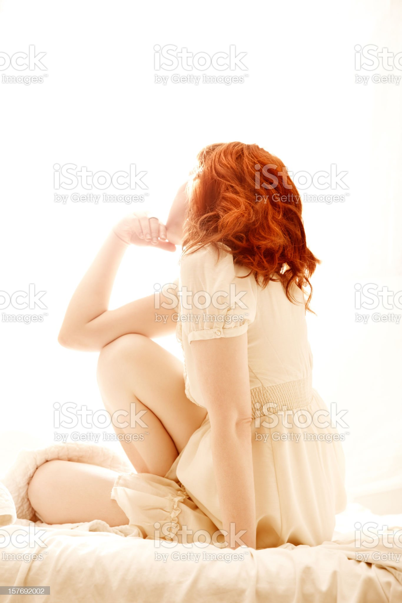 Unrecognizable redhead woman sitting in bed royalty-free stock photo