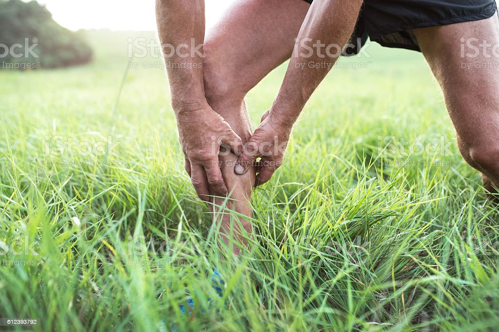 Unrecognizable runner in green field. Man with injured calf. stock photo