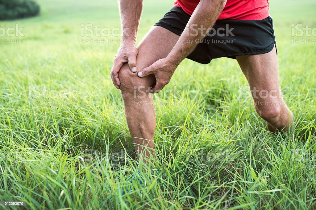 Unrecognizable runner in green field. Man with injured knee. stock photo
