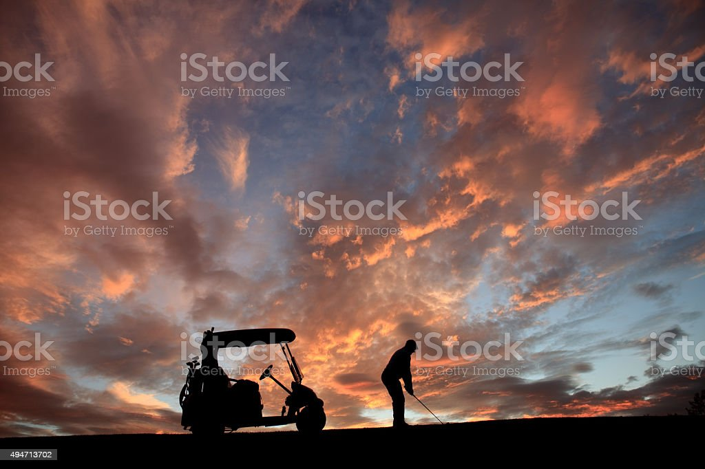 Unrecognizable Senior Golfer Swinging by His Golf Cart stock photo