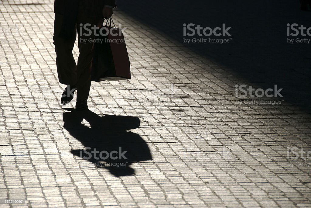Unrecognizable Shadow Man Walks Outdoors with Shopping Bag royalty-free stock photo