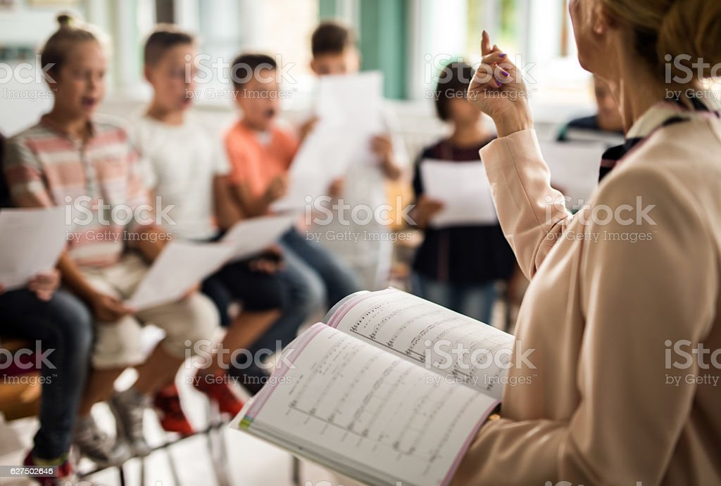 Unrecognizable teacher giving a lesson during music class. stock photo