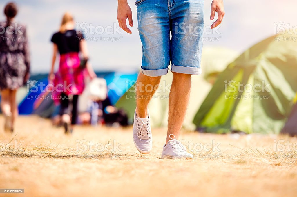 Unrecognizable teenage couple, tent festival, sunny summer, legs stock photo