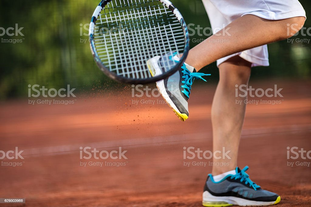 Unrecognizable tennis player cleaning shoes from dirt on the court. stock photo