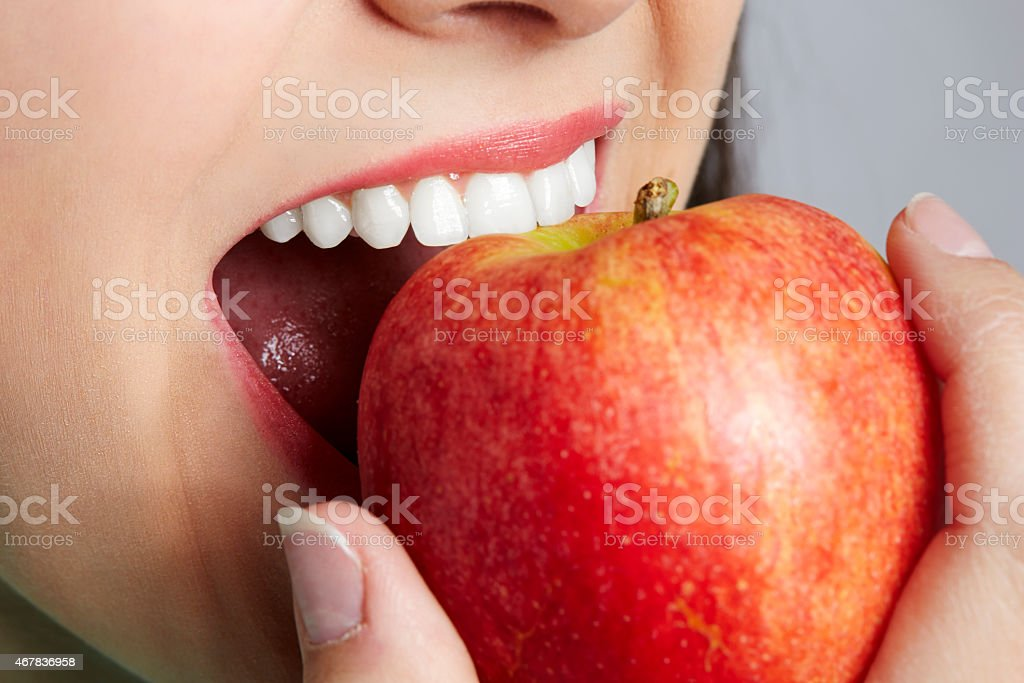 Unrecognizable woman eating red apple stock photo