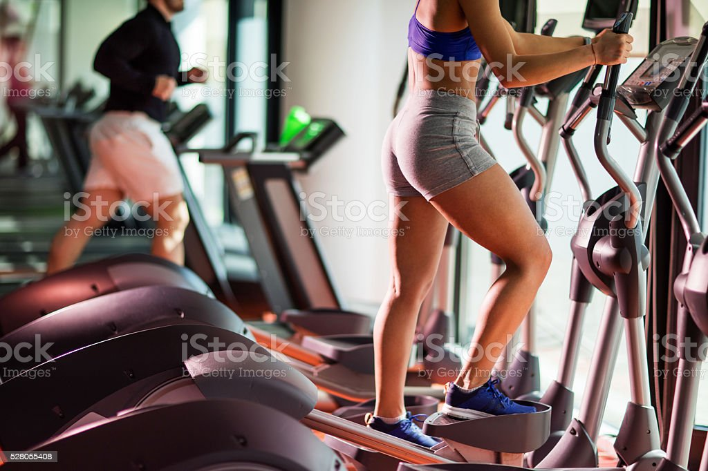 Unrecognizable woman exercising on stair climbing machine in a gym. stock photo