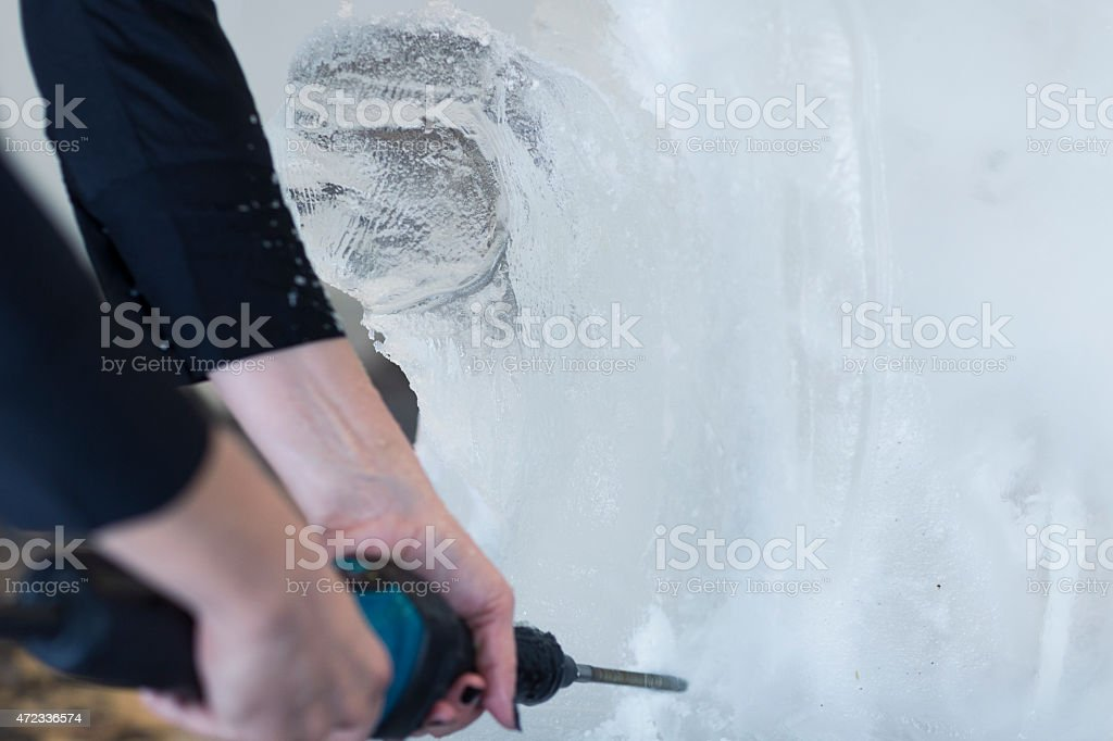 Unrecognizable Woman Making Ice sculpture. stock photo