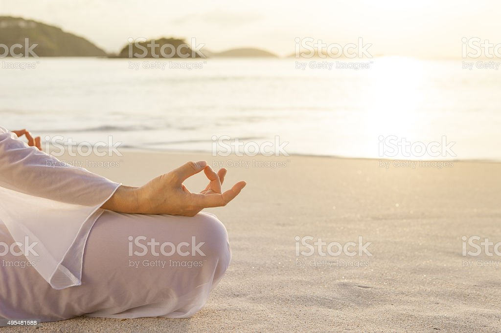 unrecognizable woman meditating at sunset on a Caribbean beach stock photo