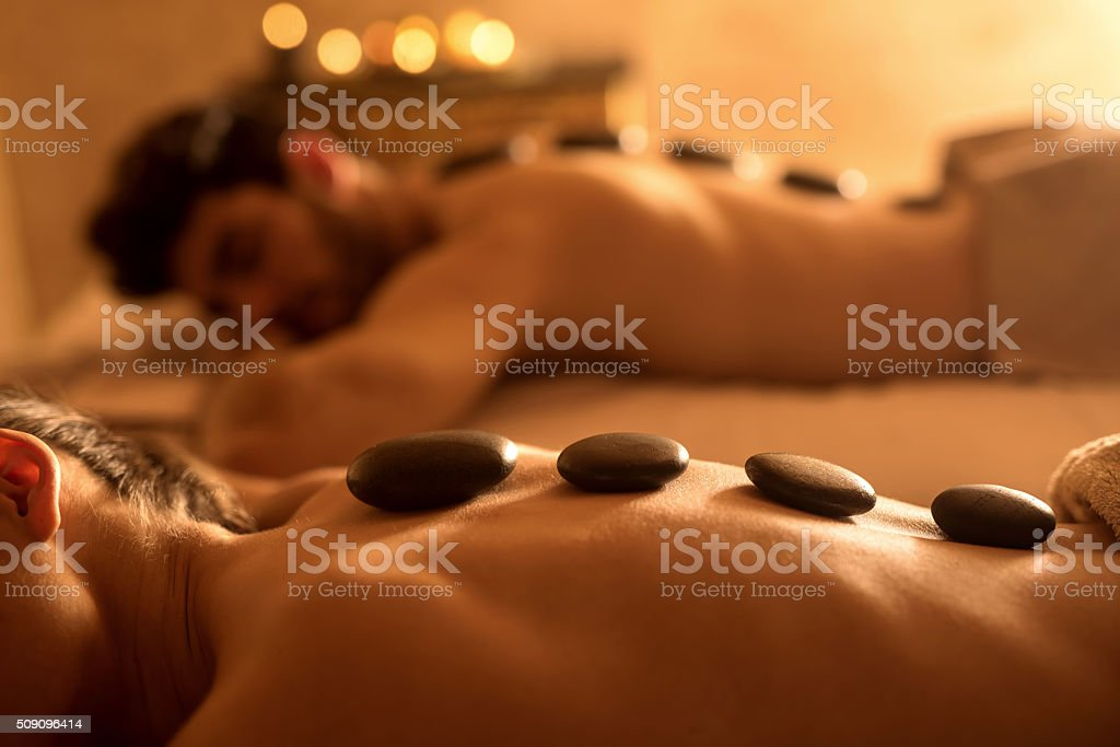Unrecognizable woman receiving hot stone therapy at spa. stock photo