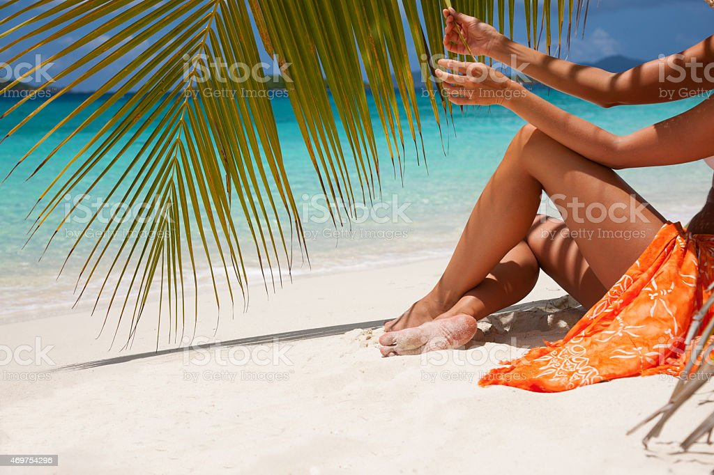 unrecognizable woman sunbathing on a tropical beach in the Caribbean stock photo