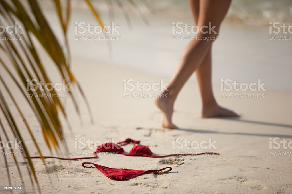 unrecognizable woman walking away from her bikini left in sand stock photo