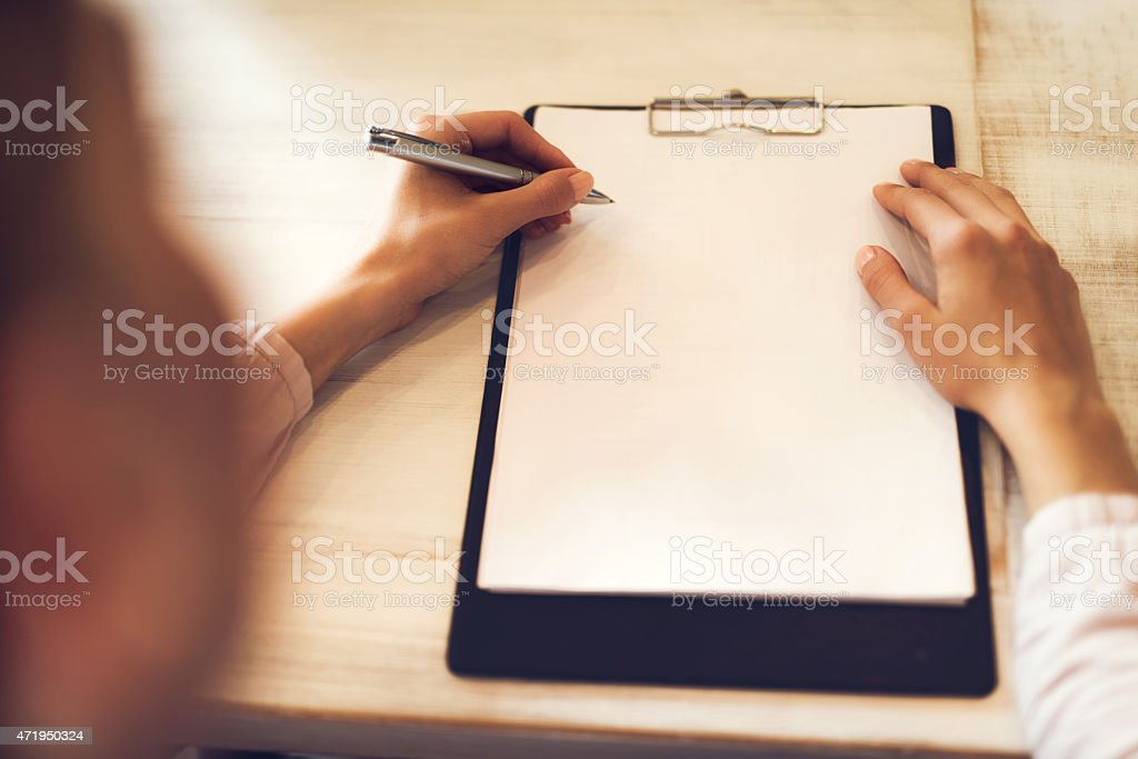 Unrecognizable woman writing on a paper. Copy space. stock photo