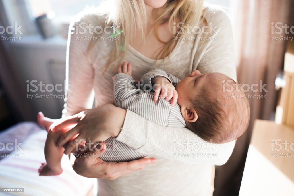 Unrecognizable young mother holding baby son in her arms stock photo