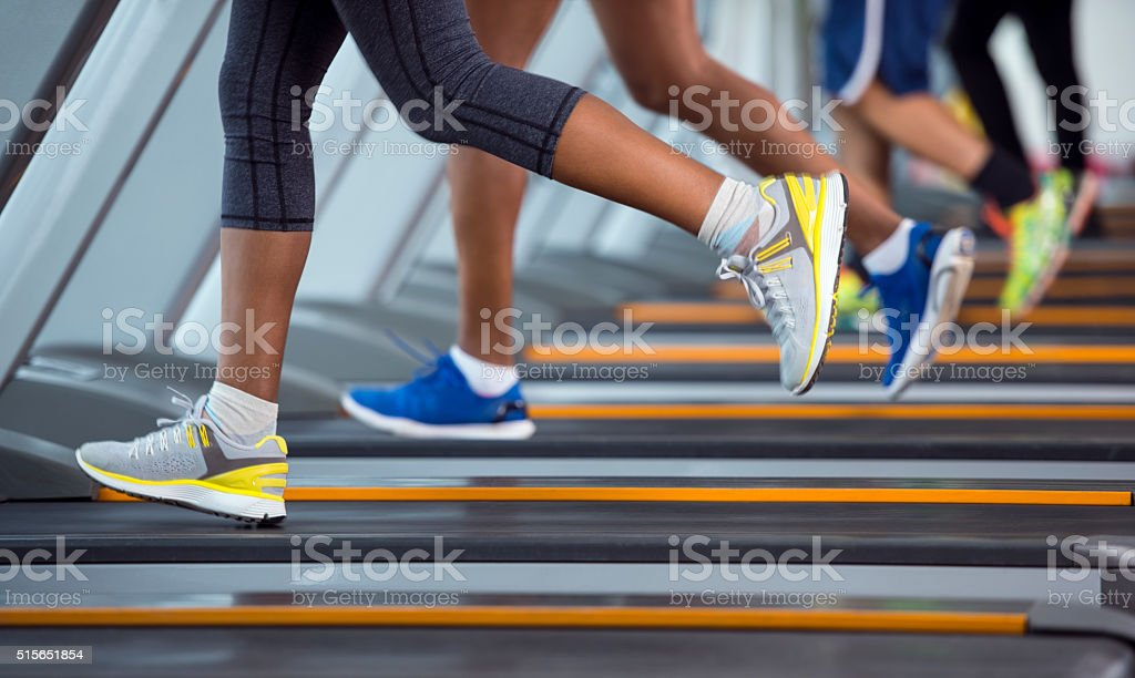 Unrecognized people running on treadmill. stock photo