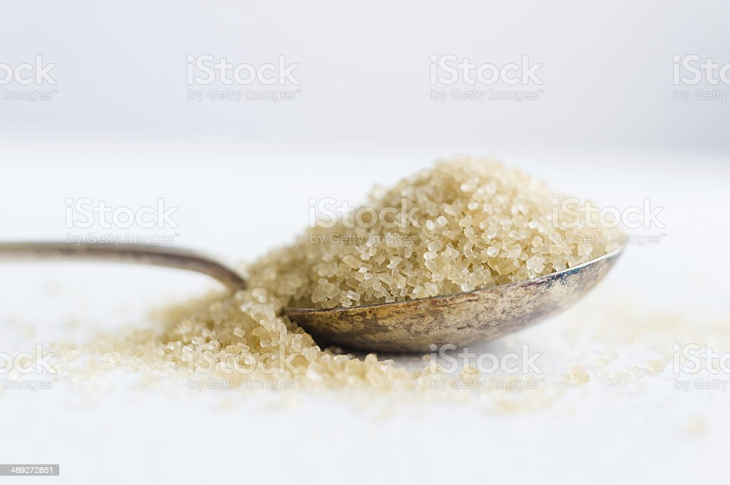 Unrefined cane sugar in rustic spoon stock photo