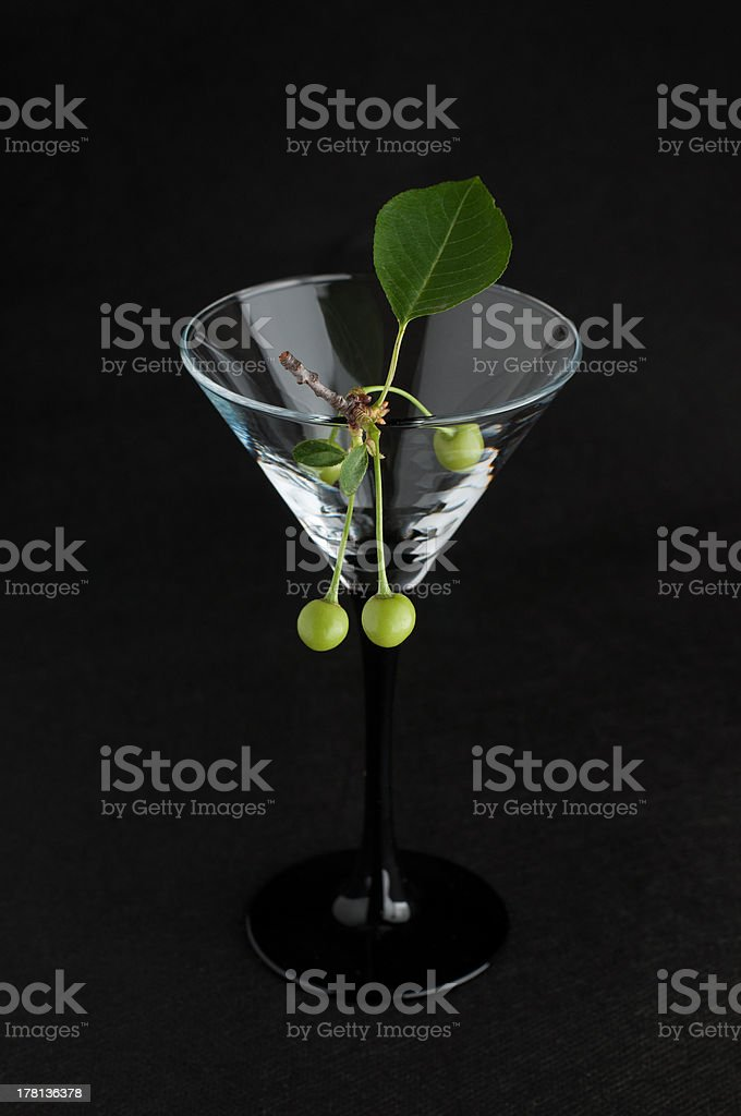 Unripe green cherry in martini glass royalty-free stock photo