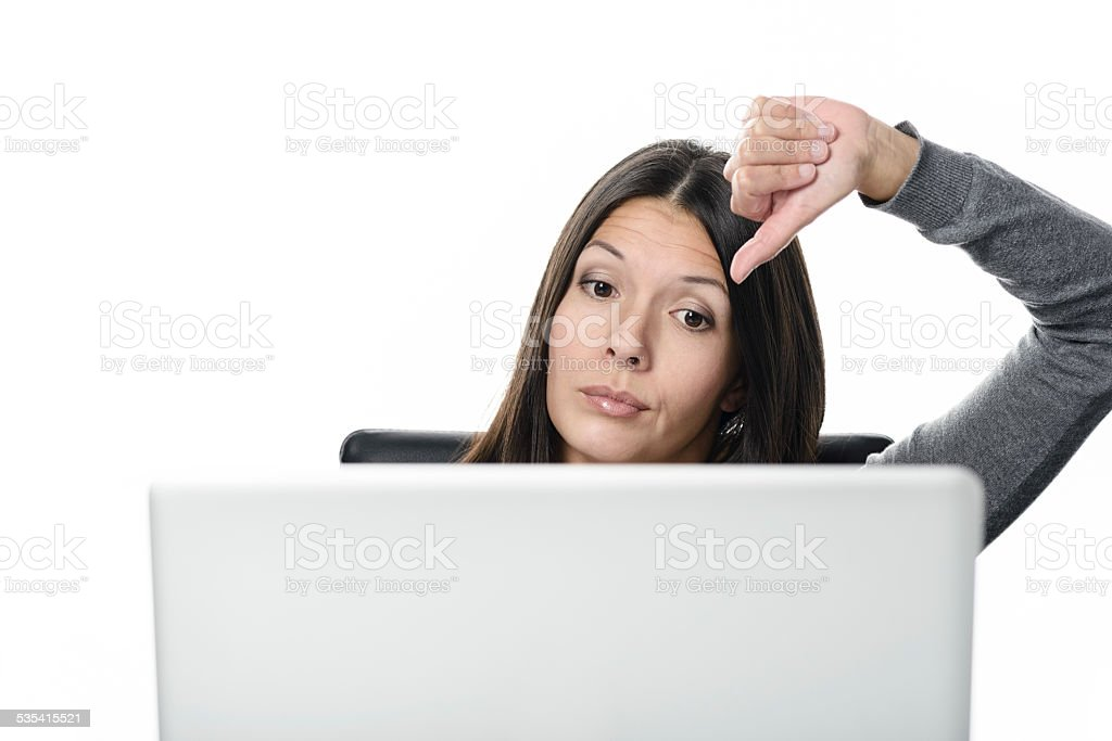 Unsatisfied Woman with Laptop Showing Thumbs Down stock photo