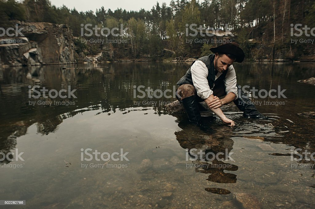unshaved gold digger washes hands in the lake with rocky stock photo