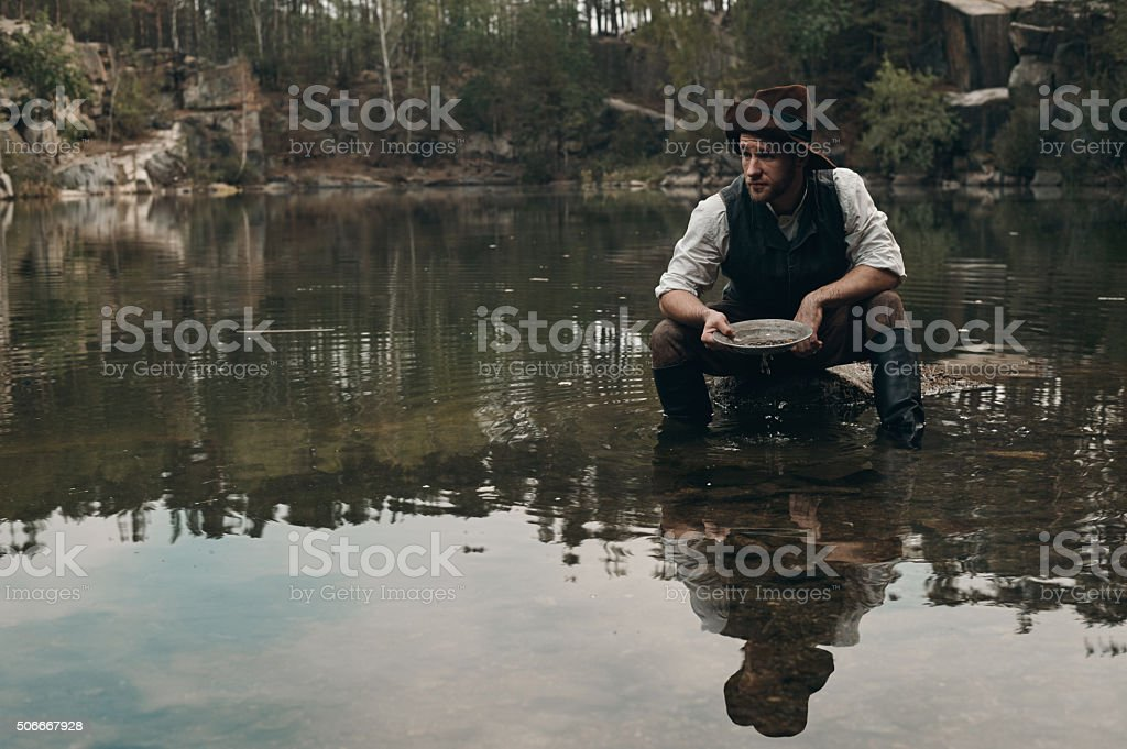 unshaved golddigger washes gold in the lake with rocky bank stock photo