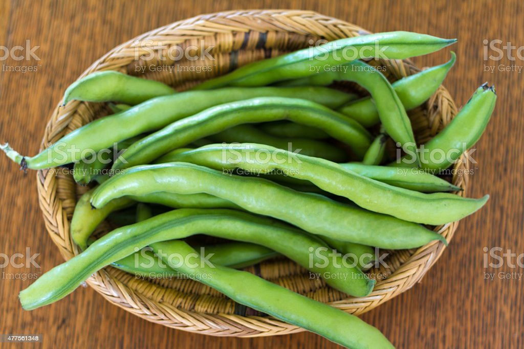 Unshelled Fava Beans (Broad Beans) in Wicker Basket stock photo
