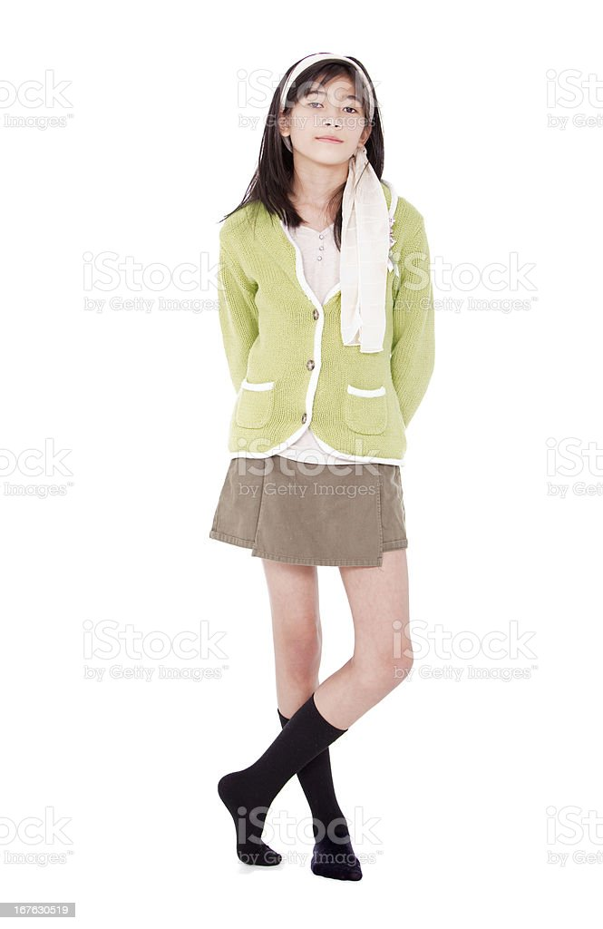 Unsmiling confident young girl in green sweater standing, isolated stock photo