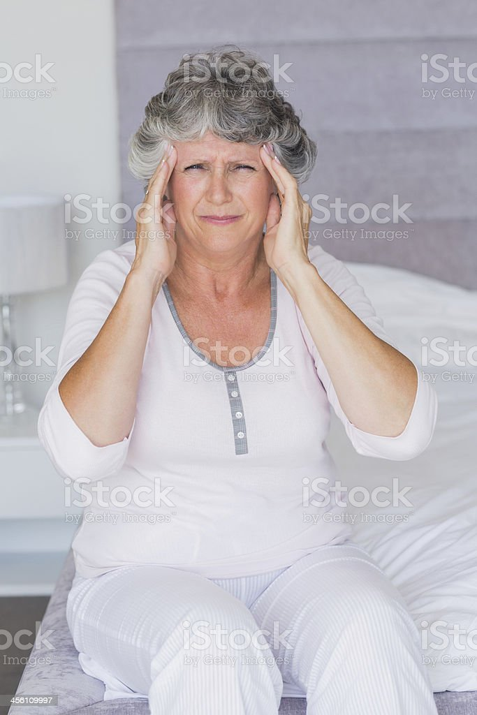 Unsmiling mature woman sitting on her bed has headache royalty-free stock photo