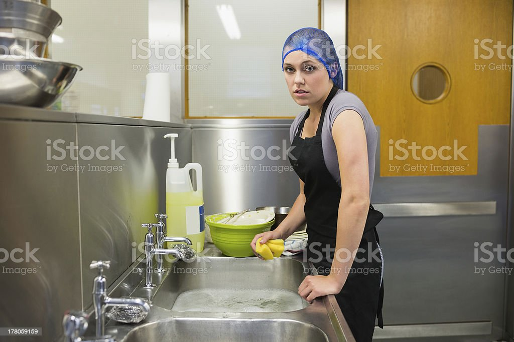 Unsmiling woman using a sponge stock photo