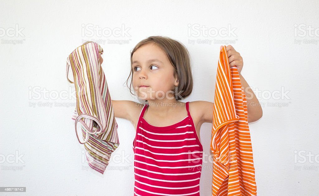 unstable little girl looking at clothings to select one stock photo