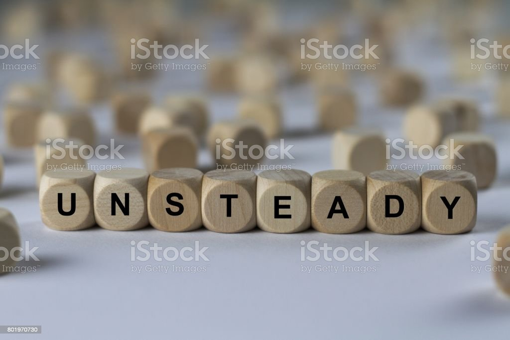unsteady - cube with letters, sign with wooden cubes stock photo