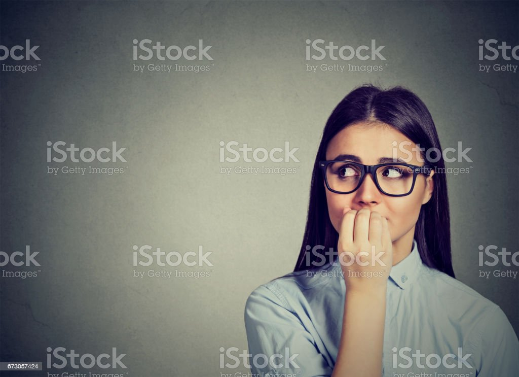 unsure hesitant woman biting her fingernails craving for something or anxious stock photo