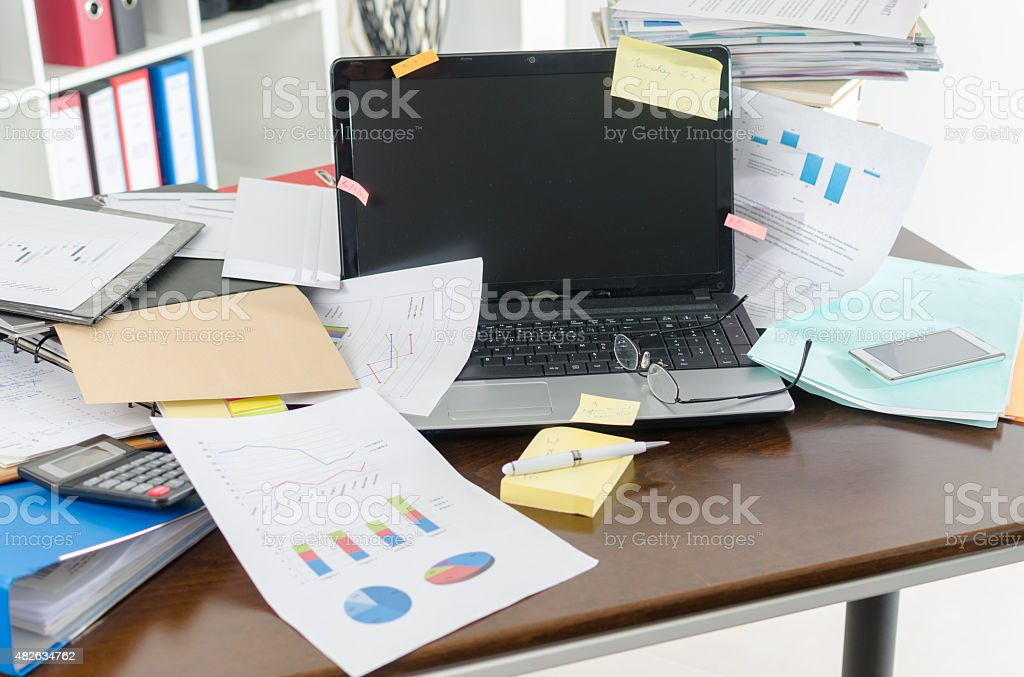 Untidy and cluttered desk stock photo