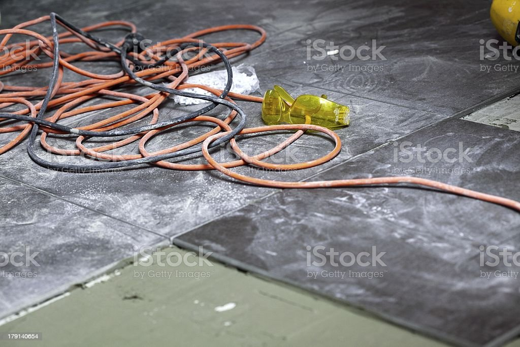 Untidy electric cables and yellow goggles on a dirty floor stock photo