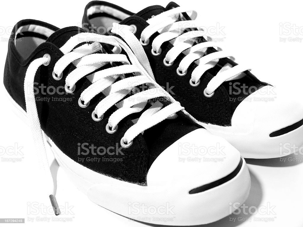 Untied Pair of Black and White Tennis Shoes stock photo