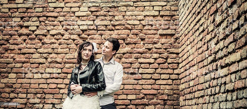 unusual wedding couple near a brick wall royalty-free stock photo