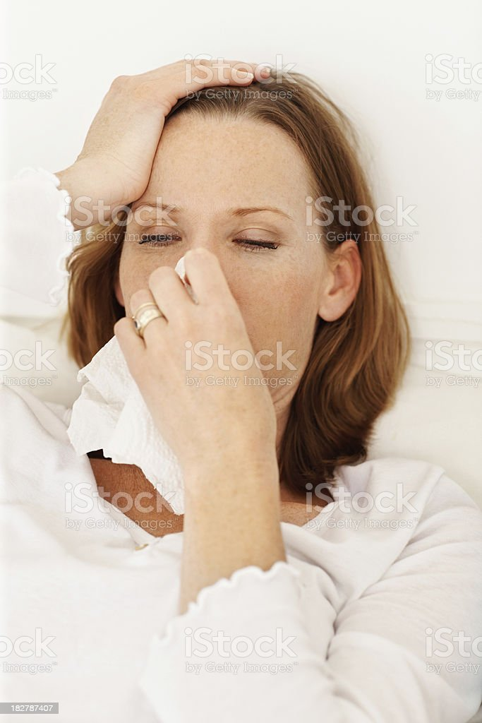 Unwell mid adult lady blowing her nose royalty-free stock photo