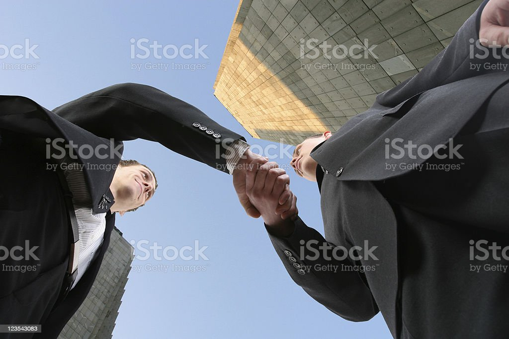 Up angle view of two men greeting stock photo