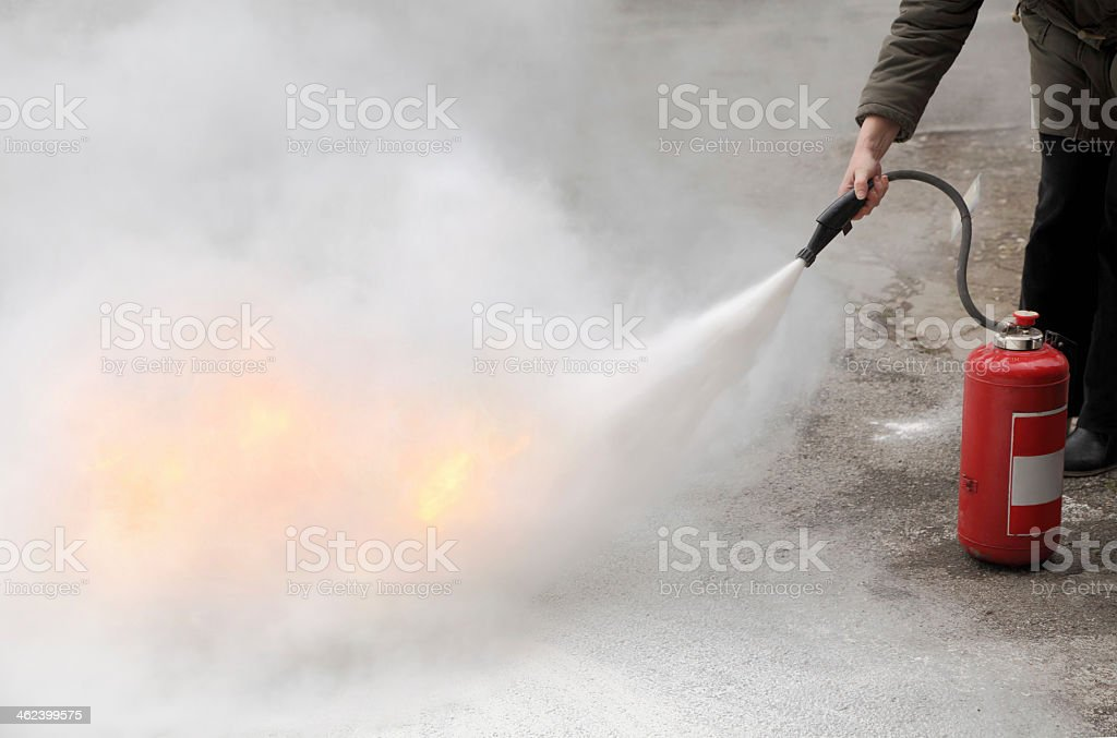 Up close Fire fighter spraying flames w/ fire extinguisher stock photo