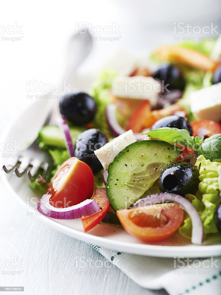 Up close photo of a Greek salad with a fork royalty-free stock photo