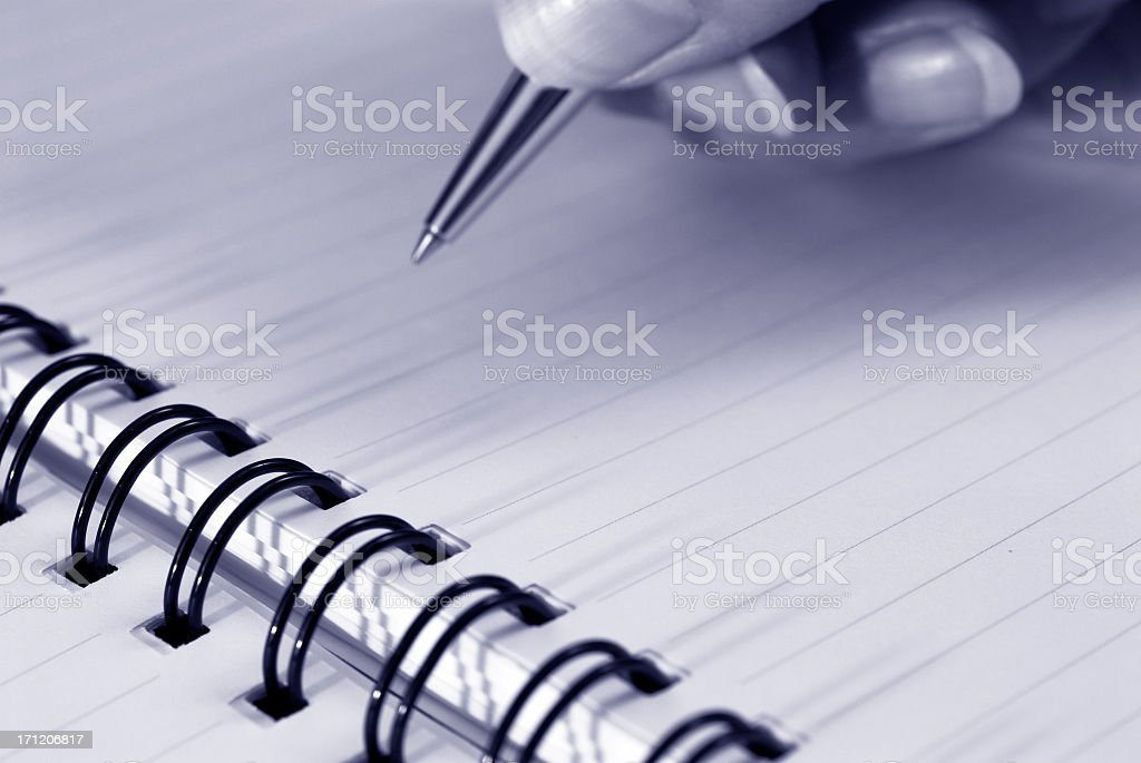 Up close view of a hand holding a pen writing in a notebook royalty-free stock photo