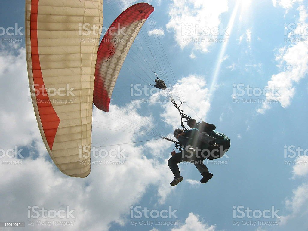 Up shot of person paragliding in the blue sky stock photo