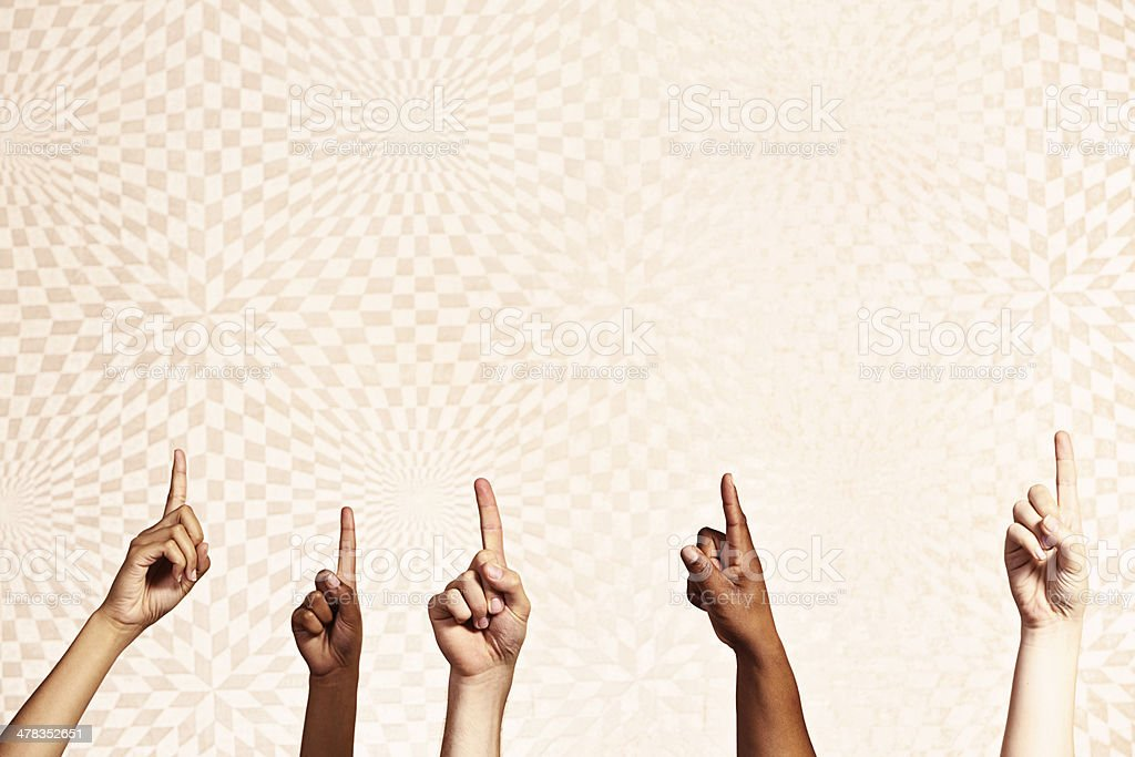 Many mixed hands point upwards enthusiastically against a...